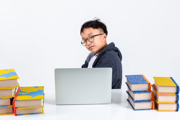 Smart boy with laptop and books