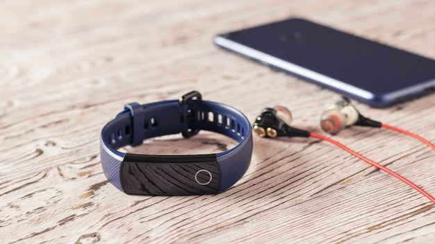 Smart bracelet, headphones and smartphone on wooden table. accessories to control sports. sports style.