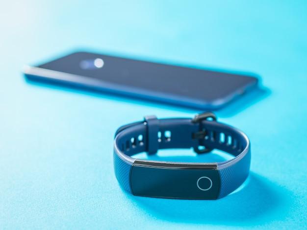 Smart bracelet and smartphone on a blue surface