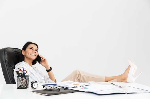 Smart brunette businesswoman talking on smartphone while sitting in armchair and working in office isolated over white wall