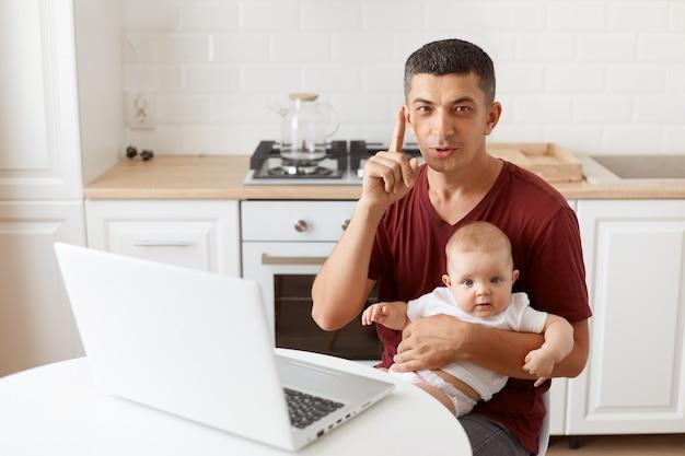 マルーンカジュアルスタイルのtシャツを着て、幼い娘と一緒にキッチンのテーブルに座って、賢いアイデアを持って、指を上げてスマートなブルネットの男性。