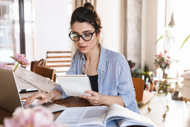 Умная брюнетка женщина в повседневной одежде печатает на ноутбуке во время работы или учебы дома