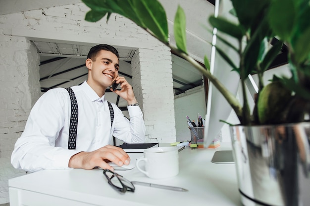 Умный бизнесмен сидит и использует компьютер для работы в офисе