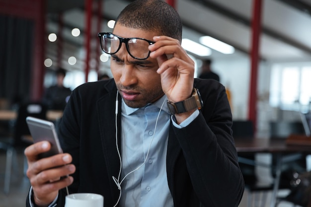 Умный бизнесмен трогает свои очки и читает сообщение на смартфоне
