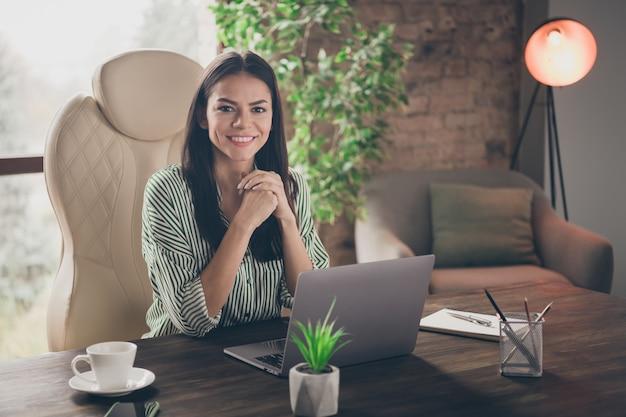 Умная бизнес-леди сидит на рабочем столе в современном офисе