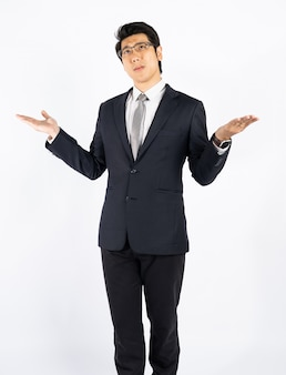 Smart businessman confused and surprised against white wall