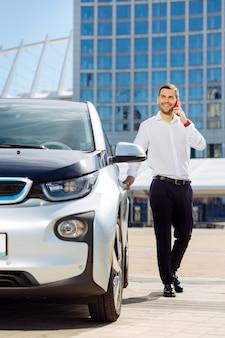 スマートビジネスマン。電話で会話しながら彼の車に来る前向きな賢い男