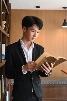 Умный бизнесмен, читающий книгу, стоя в современном офисе.