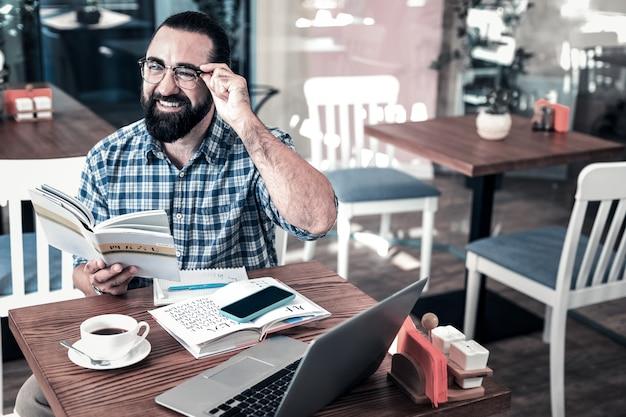 スマートビジネスマン。ビジネス会議の前に外国語を勉強しているスマートなひげを生やしたビジネスマン