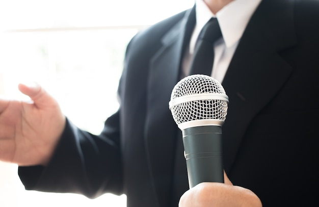 Smart businessman speech and speaking with microphones in seminar room or conference hall