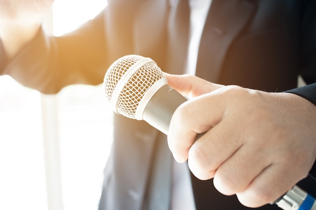 Smart businessman speech and speaking with microphones in seminar room