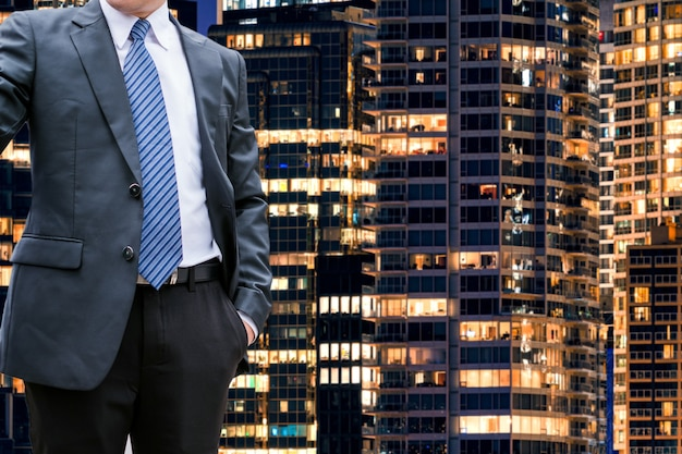 オフィスビルの照明の背景に立っているスマートビジネスマン