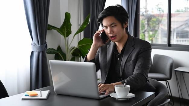 Умный бизнесмен разговаривает по мобильному телефону и использует ноутбук в офисе.