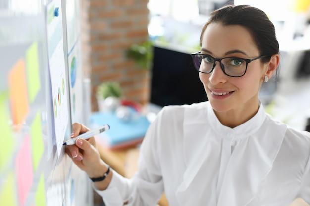 Smart businesswoman in glasses hold blue marker