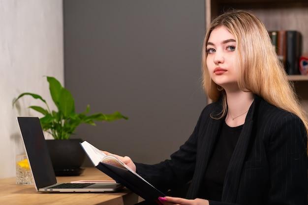 Умная деловая женщина сидит за своим столом с журналом