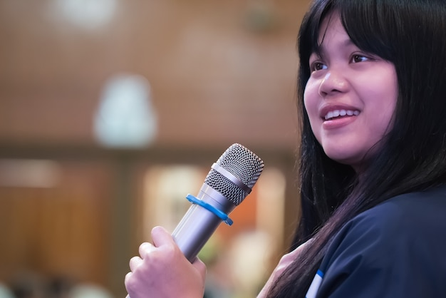 Smart businesswoman speech or speaking with microphone in seminar hall