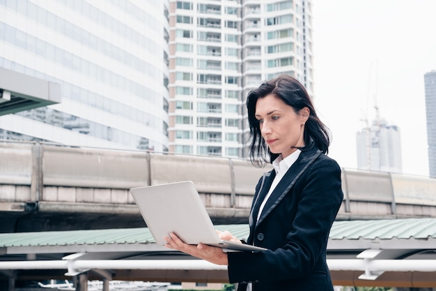 Smart businesswoman stand using laptop in the city
