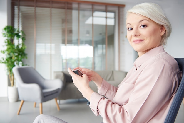 Smart businesswoman with smartphone looking at camera