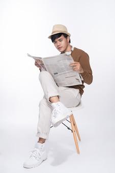 Умный случайный азиатский мужчина сидит на стуле и читает газету на фоне студии