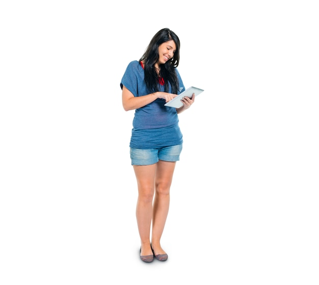 A smart casual girl using her digital tablet while standing