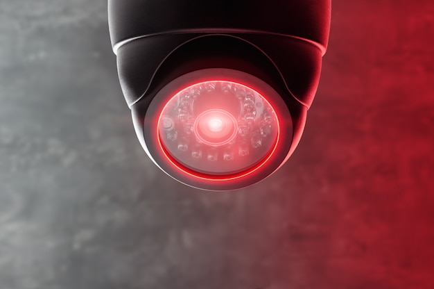 Smart cctv camera under the ceiling with red lights.