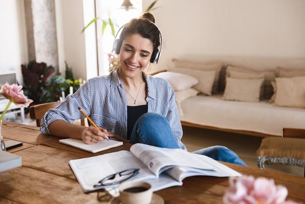 Умная очаровательная женщина в наушниках слушает музыку во время учебы с тетрадями дома