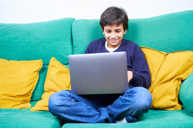Smart and cheerful child doing using laptop sitting on the sofa at home.