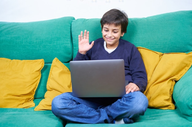 Smart and cheerful child making a video conference with laptop sitting on the sofa at home.