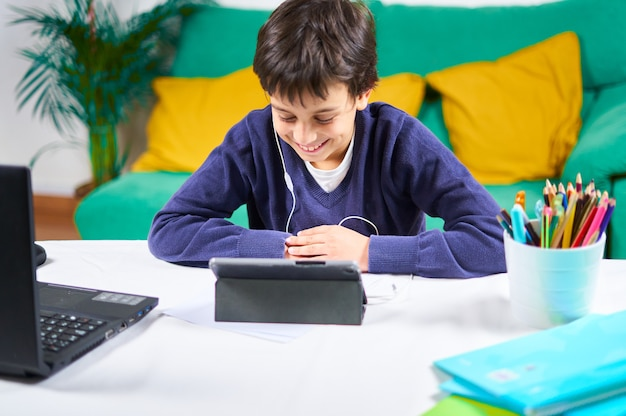 Smart and cheerful child in online classes with tablet and laptop sitting on the sofa at home.