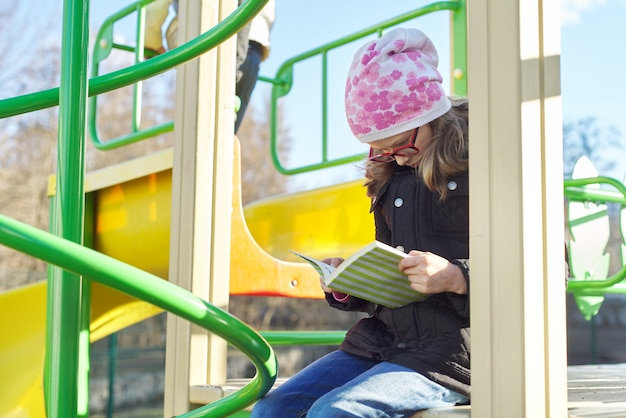 Smart child girl, 8-9 years old, in jacket hat glasses, reading book, on play area on spring day