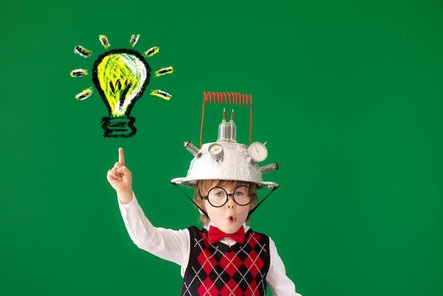 У умного ребенка есть идея. портрет ребенка против зеленой доски. забавный ребенок в шлеме с лампочкой. концепция образования, запуска и бизнес-идеи