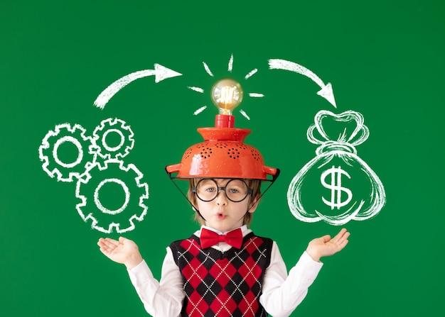 Smart child have an idea portrait of child against green chalkboard