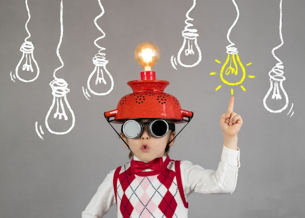 Smart child pretend to be businessman funny child wearing helmet with lightbulb