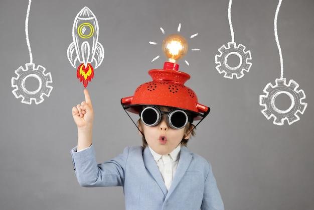 Умный ребенок притворяется бизнесменом. забавный ребенок в шлеме с лампочкой. у удивленного ребенка есть идея. концепция образования, искусственного интеллекта и бизнес-идеи