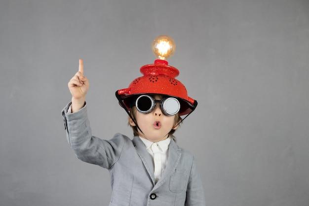 똑똑한 아이는 사업가 인 척합니다. 전구와 헬멧을 착용하는 재미있는 꼬마. 교육, 인공 지능 및 사업 아이디어 개념