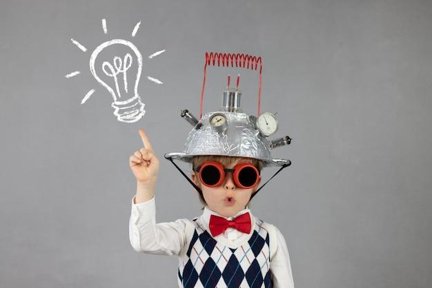 賢い子供は、電球付きのヘルメットをかぶったビジネスマンの面白い子供になりすます