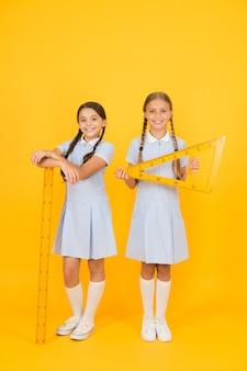 茎のレッスンで賢い子供たち。女の子は幾何学が大好きです。古い学校。現代教育。レトロな制服を着た幸せな友達。ヴィンテージキッズファッション。学校に戻る。小さな女の子は数学の道具を持っています。 stem分野。