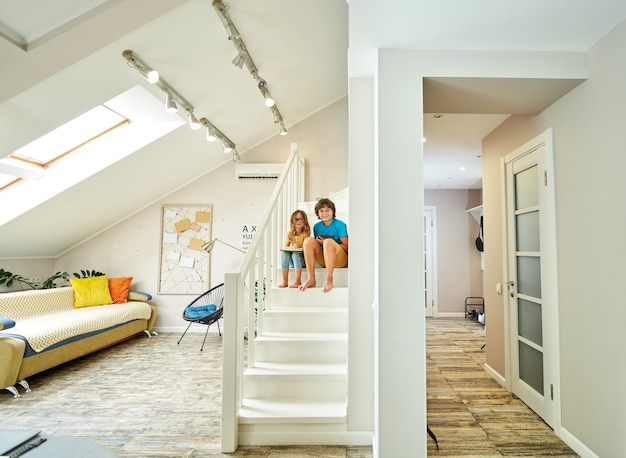 집에서 공부하는 똑똑한 아이들은 계단에 앉아 있는 형제 자매의 전체 길이 샷과