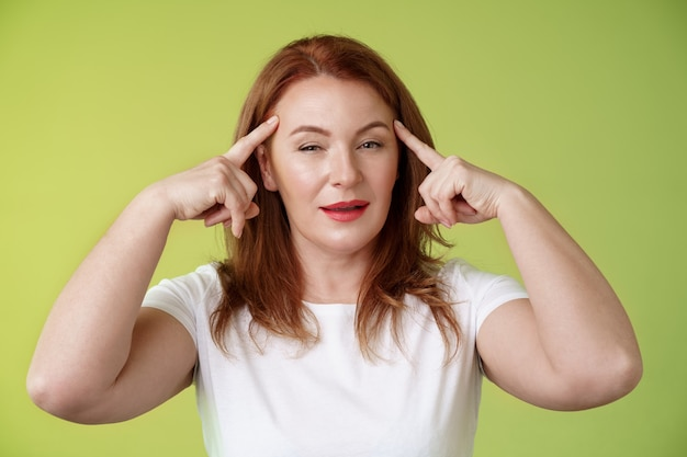 賢い選択興味をそそられる思慮深い見栄えの良い断定的な赤毛創造的な中年の女性は寺院に目を細めて熟考する情報思考を使用する精神力を読む心は緑の壁に立つ