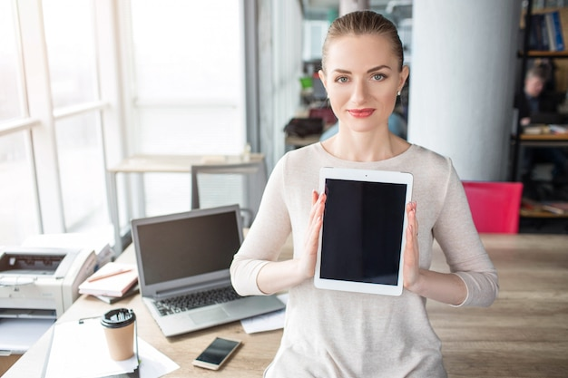 Smart and confident woman is looking to the camera and holding a tablet in it