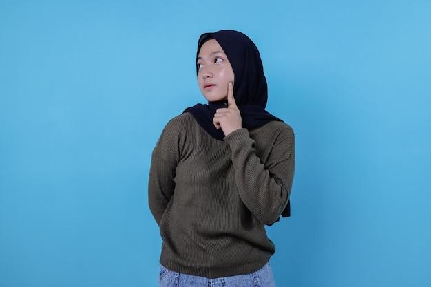 真面目でクリエイティブなスマートな女性の同僚が、青い壁に思慮深くあごに触れることを選択することを考え、深い焦点を考えています。