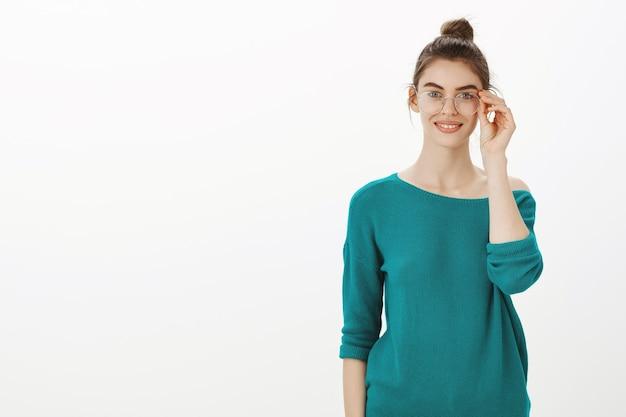 Giovane donna intelligente e creativa con gli occhiali sorridendo soddisfatta sopra il muro bianco