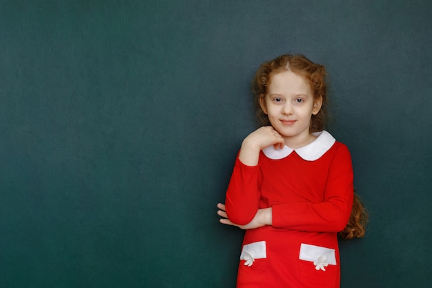 教室で緑の黒板の近くのスマートな巻き毛の少女。教育の概念