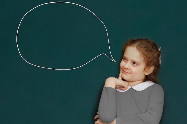 教室で緑の黒板の近くのスマートな巻き毛の少女。