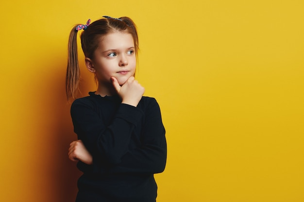 Умная милая очаровательная девочка трогает щеку и смотрит вверх, думая
