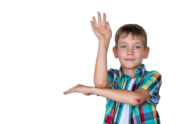 A smart, cute boy raises his hand to answer in class. happy child against a white board. education concept, concept back to school
