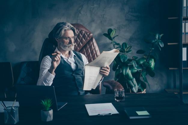 Умный денди старый бизнесмен сидеть на стуле, читать ретро-журнал, курить сигарету в офисе