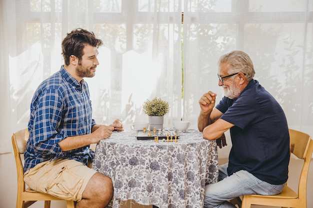 Smart elder playing chess board game at home care with younger man for stay brain healthy