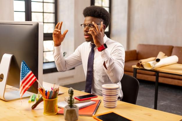コンピューターの画面を見ながら手を上げて賢い感情的な男