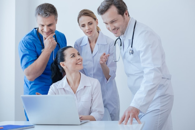 Smart energetic delighted therapists working and using innovative laptop at the clinic while enjoying conversation and sharing opinions